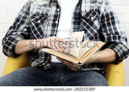 Young man reading book, close-up, on light background - stock photo