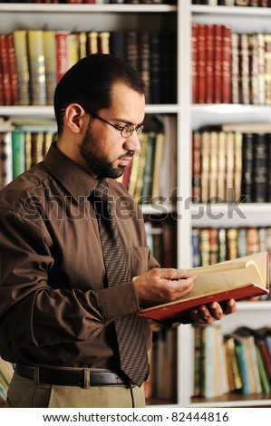 Young man reading book in library - stock photo