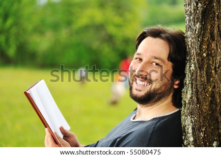 Young man reading book in nature - stock photo