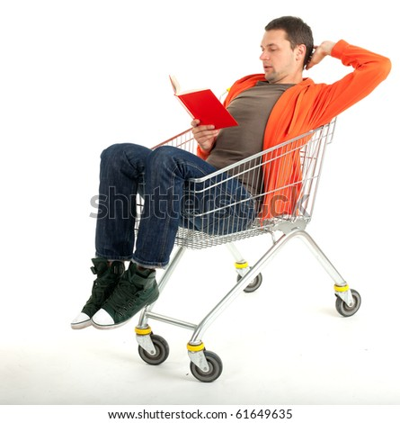 young man reading book in shopping cart