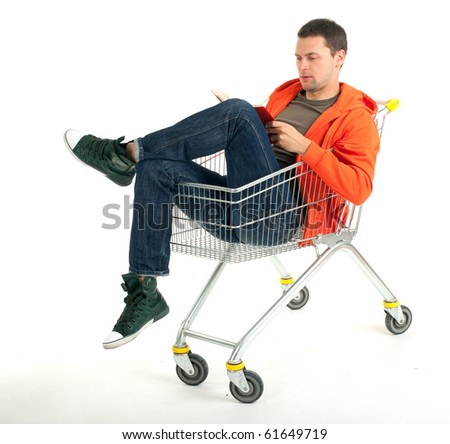 young man reading book in shopping cart - stock photo