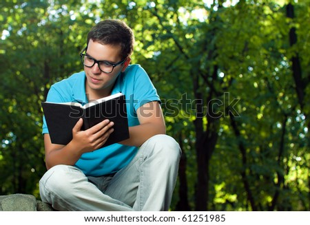 young man reading book in the park - stock photo