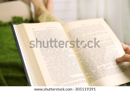 Young man reading book on sofa close up