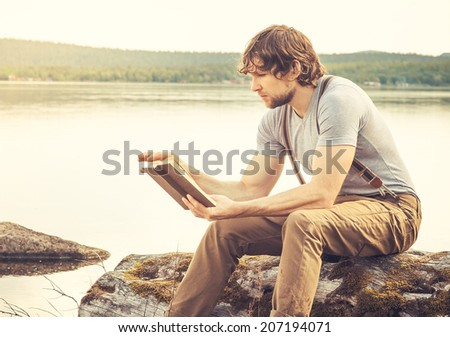 Young Man reading book outdoor with lake in background- summer vacations and Lifestyle concept - stock photo