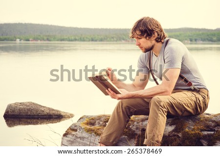Young Man reading book outdoor with scandinavian lake on background Education and Lifestyle Travel concept - stock photo