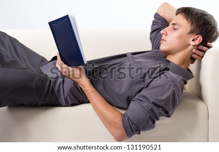 Young man reading book while lying at the couch - stock photo