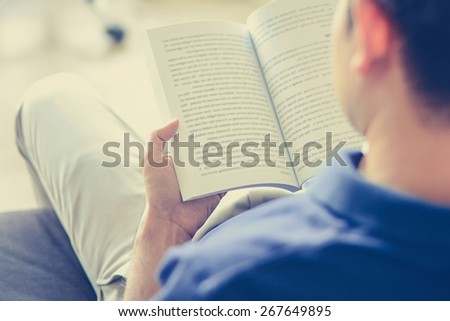 Young man reading book while sitting on the couch (over shoulder view) - vintage tone, soft focus - stock photo