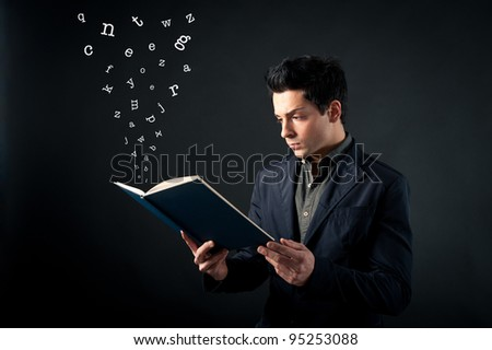 Young man reading book with letters coming out against dark background. - stock photo