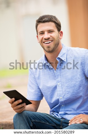 Young man reading E-book outside on steps - stock photo