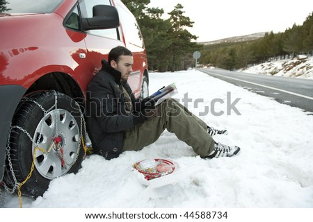 Young man reading instructions to install snow chains on his car. - stock photo