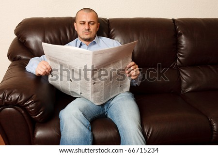 Young man reading newspaper on a leather sofa - stock photo