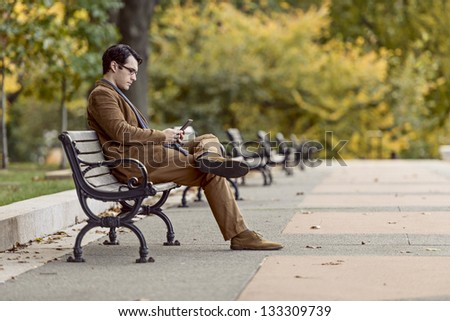 Young Man Reading On A Digital Tablet At The Park - stock photo