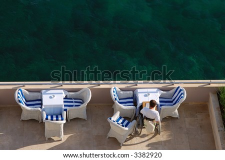 Young man reading on a hotel terrace - stock photo
