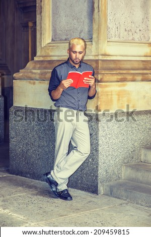 Young Man Reading Outside. Wearing a black patterned shirt, grey pants, leather shoes, hands holding a red book, a young guy with beard, yellow hair, is standing against a column, reading.  - stock photo