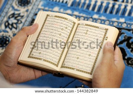 Young man reading the Holy Koran at the mosque