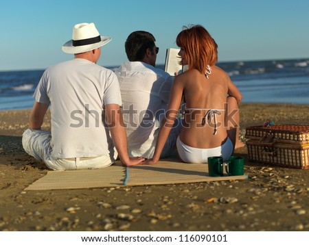 young man reading, while his girlfriend is holding hands with another man, at a picnic by the sea shore - stock photo