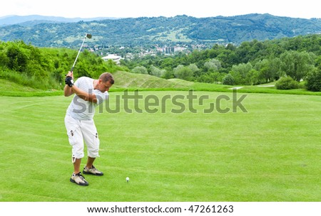 Young man ready to strike ball on golf course.