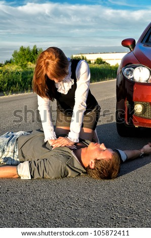 Young man reanimation on a road. Concept first aid - stock photo