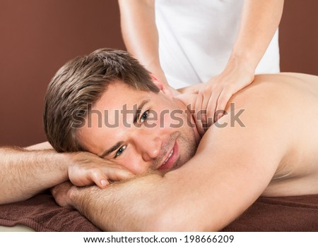 Young man receiving back massaging in spa