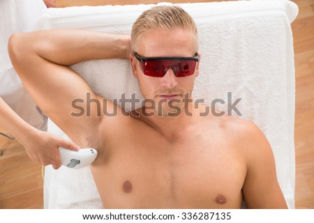Young Man Receiving Laser Epilation Treatment From Beautician At Beauty Center - stock photo