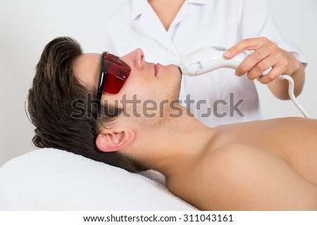 Young Man Receiving Laser Hair Removal Treatment At Beauty Center - stock photo