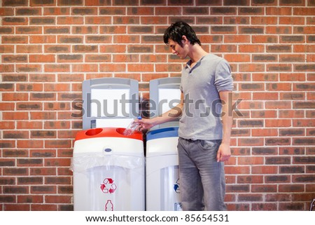Young man recycling a plastic bottle - stock photo