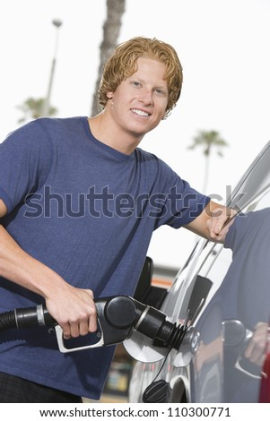 Young man refueling his car - stock photo
