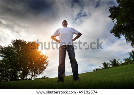 young man relax on green field in sunset time