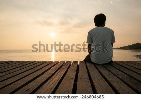 Young man relax siting on pier looks forward with sunset sky  - stock photo