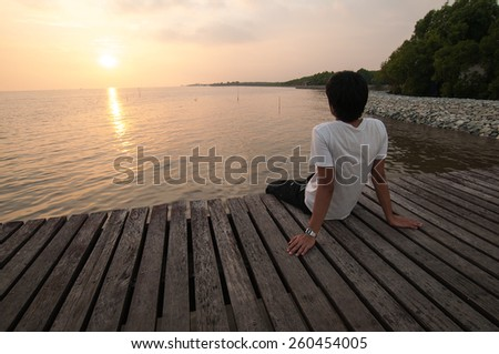 Young man relax siting on pier looks to forward with sunset sky - stock photo
