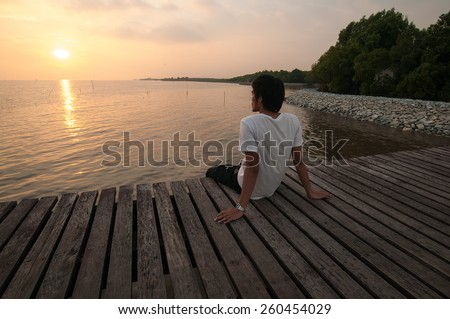 Young man relax siting on pier looks to left with sunset sky - stock photo