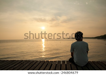 Young man relax siting on pier looks to right with sunset sky. Conceptual for thinking and looking for concentrate somethings. Summer background with copy space. Summer concept for label text banner. - stock photo