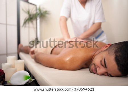 Young man relaxed in spa center - stock photo