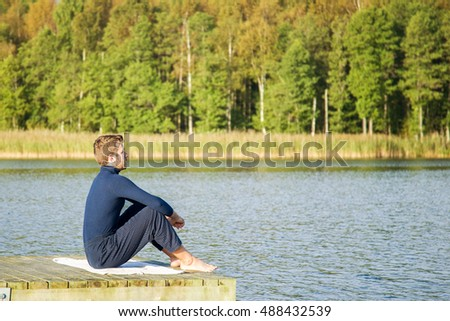 Young man relaxing and practicing yoga on the lake footbridge early morning in autumn.
