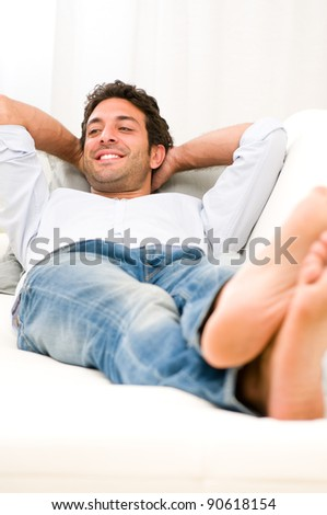 Young man relaxing and taking a break on sofa at home - stock photo