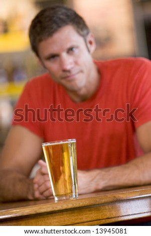 Young man relaxing at a bar with a beer - stock photo