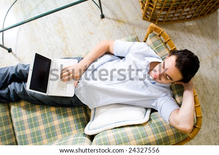 young man relaxing at home with a laptop computer - stock photo