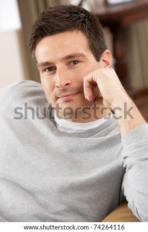 Young Man Relaxing In Chair At Home - stock photo