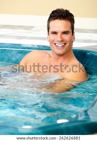 Young man relaxing in hot tub. Summer vacation. - stock photo