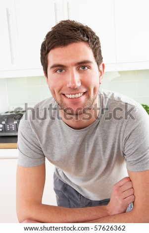 Young Man Relaxing In Modern Kitchen - stock photo