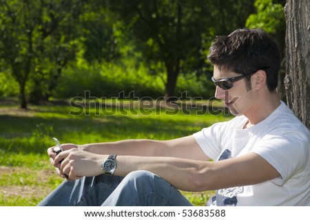 Young man relaxing in the park with his mobile phone