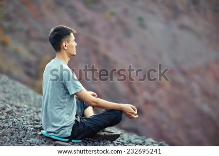 Young man relaxing in yoga position on rocky cliff  - stock photo