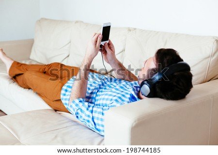 Young man relaxing on a sofa and listening to music on his smartphone - stock photo