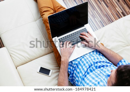 Young man relaxing on a sofa with a laptop and mobile - stock photo