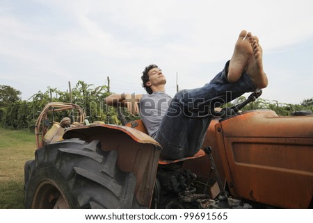 Young man relaxing on a tractor in the country