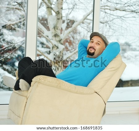 Young man relaxing on a white sofa at home by winter snow time - stock photo