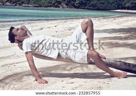 Young man relaxing on an old tree at the beach lying on his back looking into the sun with closed eyes as he enjoys a hot summer day in the tropics while on vacation - stock photo