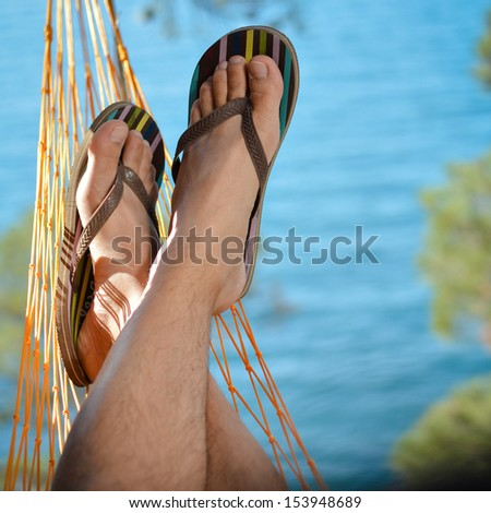 Young man relaxing on hammock in summer outdoors on beach with blue sea on the background - stock photo
