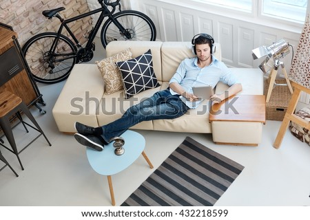 Young man relaxing on sofa, using tablet computer, listening to music at home. - stock photo