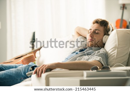Young man relaxing on sofa with headphones in the living room. - stock photo